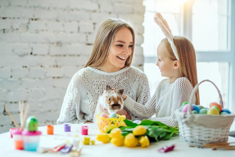 Preparing for Easter with my mother.The little daughter with her mother stroke a home decorative rabbit stock photo