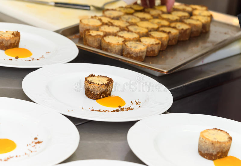 Preparing food in restaurant kitchen. Preparing dessert in a restaurant kitchen, plates and tray with food stock photography