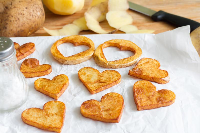 Preparing a food for Valentine`s Day abstract love concept witch french fries chips heart shape. On white background stock photography