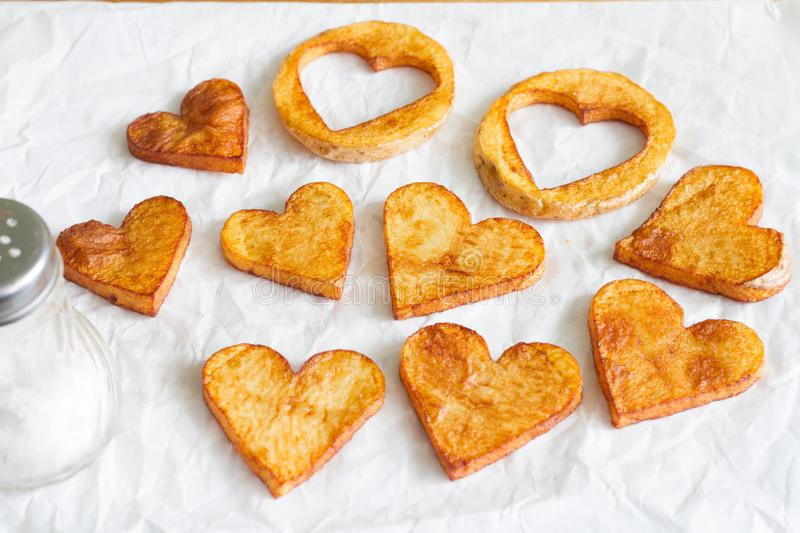 Preparing a food for Valentine`s Day abstract love concept witch french fries chips heart shape. On white background stock photos