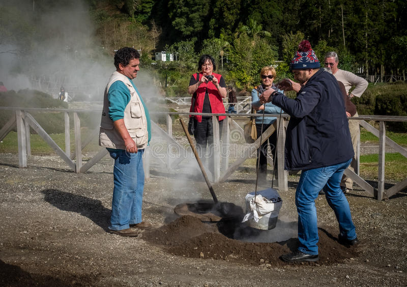 Preparing Furnas stew. Two men closing the volcanic vent after taking out the traditional Furnas stew which is cooked for many hours in the volcanic vents in the stock photos