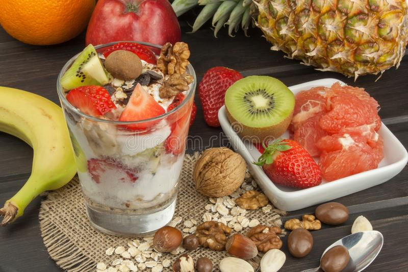 Preparing healthy breakfast for kids. Yogurt with oatmeal, fruit, nuts and chocolate. Oatmeal for breakfast. Preparing diet meals. A healthy diet for athletes stock photography