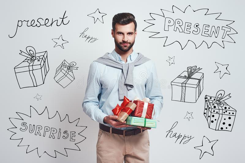 Preparing for holidays. Handsome smiling man is holding gifts for friends while standing against grey background with royalty free stock images