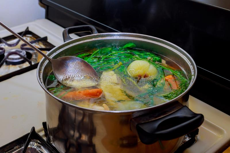 Preparing homemade chicken soup with vegetables in metal pan. Homemade preparing chicken soup with vegetables in metal pan broth with herbs, boiling, saucepan stock image