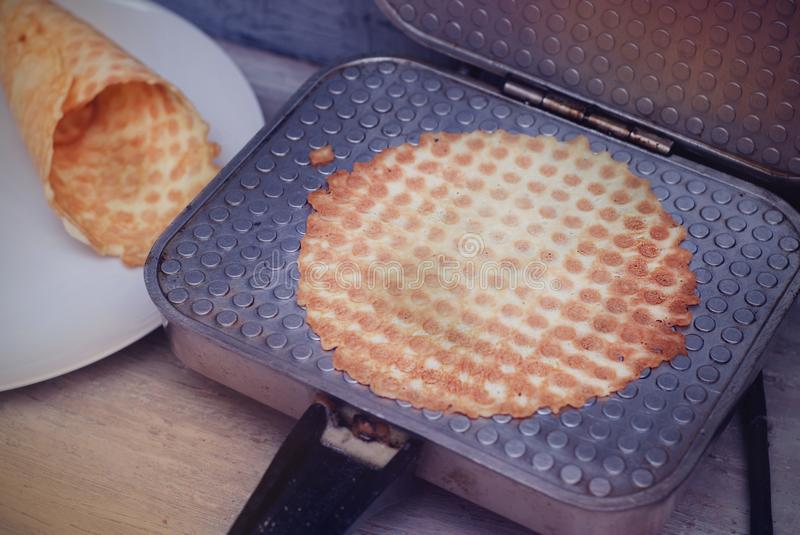 Preparing Homemade Waffles by waffle maker machine. Waffle Tubes or Rolls. Dessert. Food Preparing Proces. stock images