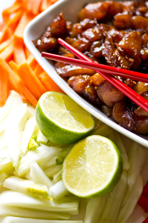 Preparing Korean food. Preparing Asian (oriental, Korean) food - bowl of chicken meat in soy sauce ready to be fried with red chopsticks royalty free stock images