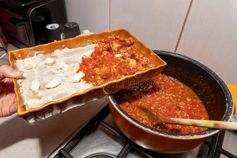 Preparing lasagna in a home kitchen. Cooking homemade meals for the household royalty free stock image