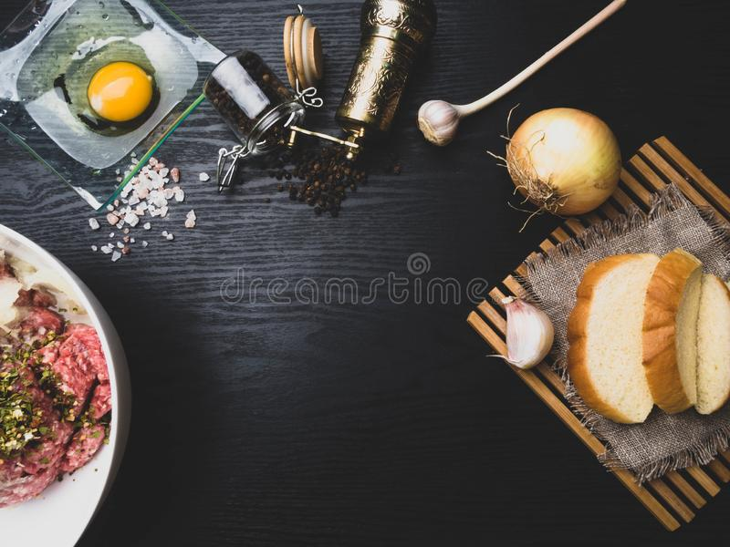 Preparing meatball with ingredients, such as egg, meat, bread, onion, garlic, herbs on wooden board, copy space royalty free stock image