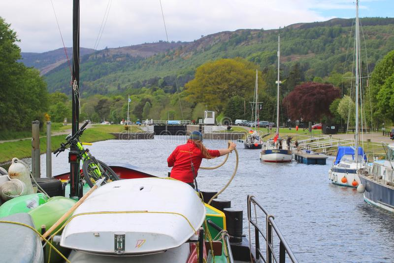 Preparing mooring rope approaching lock. Crew member preparing mooring rope before entering Dochgarroch Lock on the Caledonian Canal in Scotland stock photos