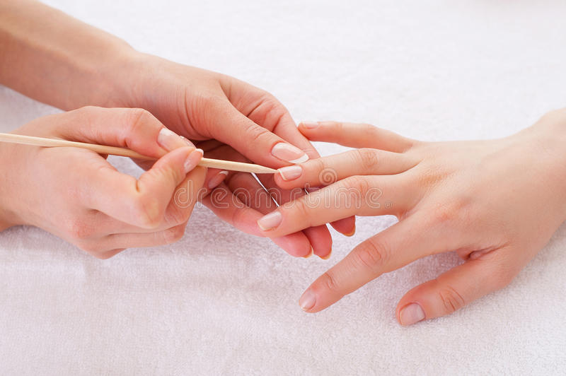 Preparing nails for manicure. Close-up of manicure master preparing customers nails for manicure stock photography