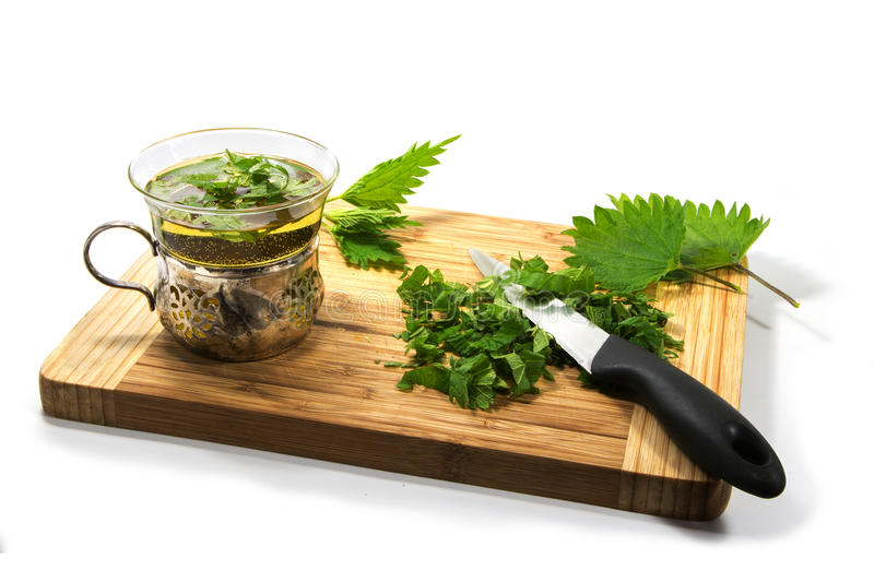 Preparing nettle tea, leaves, knife and teacup on a wooden cutting board on a white background. Preparing nettle tea, leaves, knife and teacup on a wooden stock image