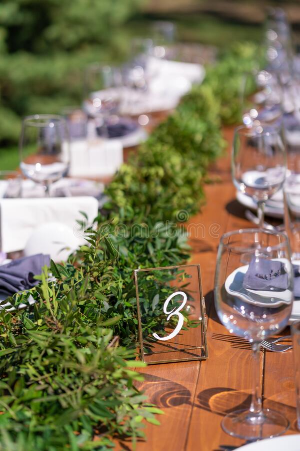Preparing for an open-air party. Decorated with fresh flowers served tables. Table number. Decoration Details stock photography