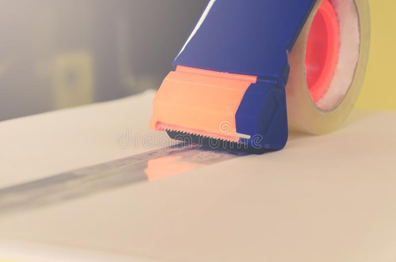 Preparing parcel for shipping with scissors and scotch tape cutter. Close - up of parcel box with scissors and scotch tape cutter, Preparing a parcel or package stock photo