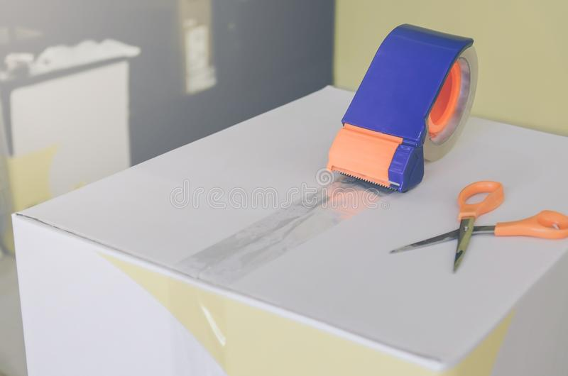 Preparing parcel for shipping with scissors and scotch tape cutter. Close - up of parcel box with scissors and scotch tape cutter, Preparing a parcel or package royalty free stock image