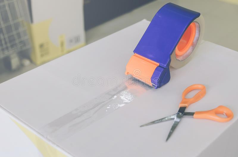 Preparing parcel for shipping with scissors and scotch tape cutter. Close - up of parcel box with scissors and scotch tape cutter, Preparing a parcel or package stock image