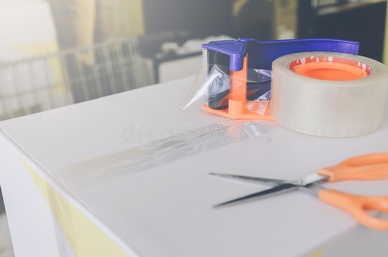 Preparing parcel for shipping with scissors and scotch tape cutter. Close - up of parcel box with scissors and scotch tape cutter, Preparing a parcel or package stock images