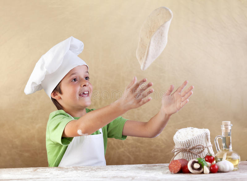 Preparing the pizza dough. Boy with chef hat preparing the pizza dough - kneading and stretching royalty free stock photo