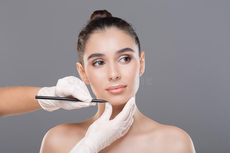 Doctor drawing lines on female face, gray studio background. Preparing for plastic surgery. Doctor drawing lines on female face, gray studio background stock photography