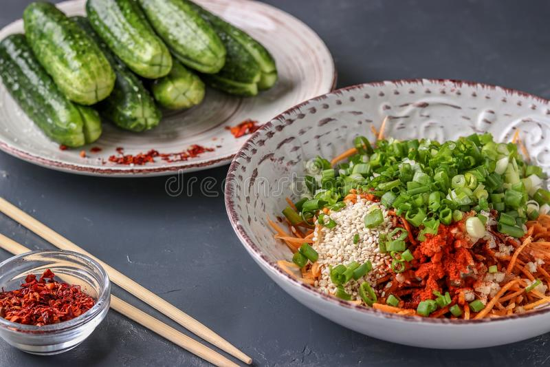 Preparing products for cooking traditional Korean cucumber kimchi snack: mixing ingredients in a bowl, fermented food, horizontal stock photos