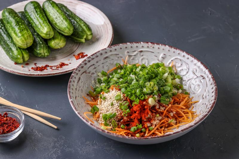 Preparing products for cooking traditional Korean cucumber kimchi snack: mixing ingredients in a bowl, fermented food, horizontal stock photo