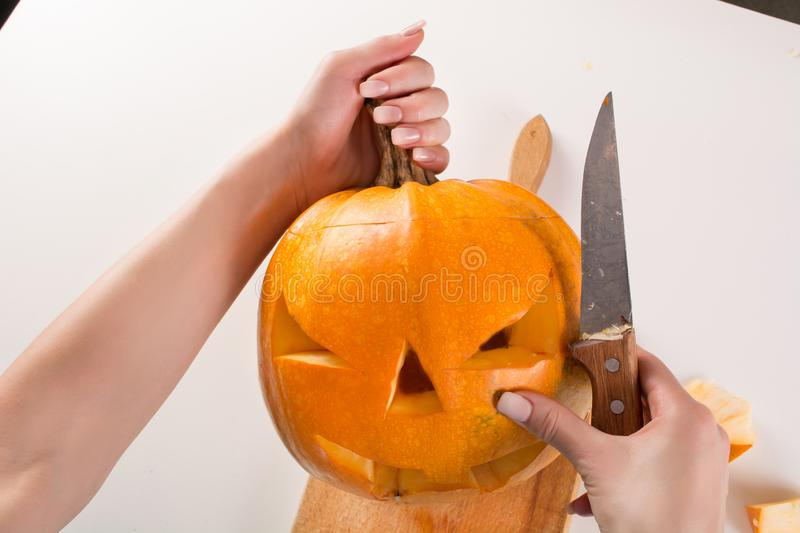 Preparing pumpkin for Halloween holiday on kitchen board royalty free stock photos