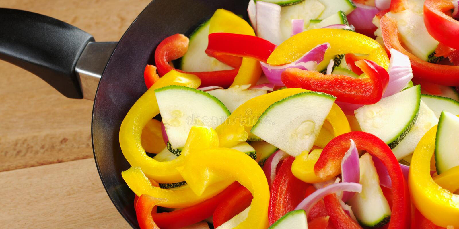 Preparing Ratatouille. The raw ingredients of ratatouille in a frying pan. Ratatouille is a light summer French dish which mainly consists of zucchini, pepper stock image