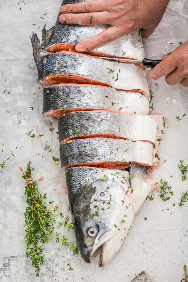 Preparing salmon in the summer garden for grill. On white table stock image