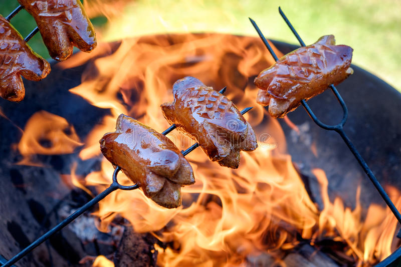 Preparing sausages on camp fire royalty free stock photo