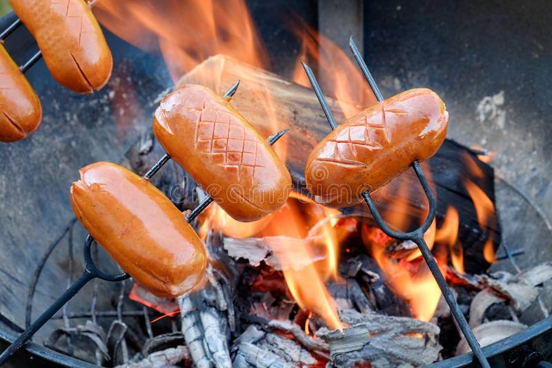 Preparing sausages on camp fire stock photos