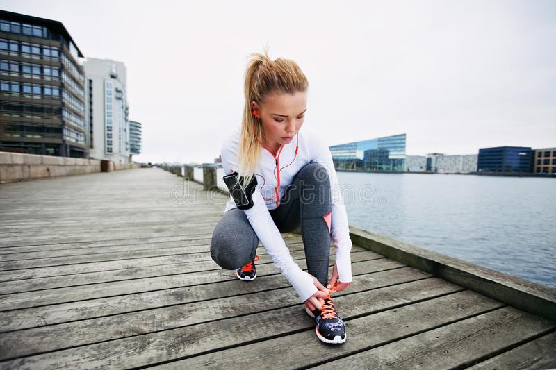 Preparing for a sprint. Young woman tying her shoelaces before a run along waterfront. Female runner preparing foe sprint. Fit female athlete on boardwalk along stock image
