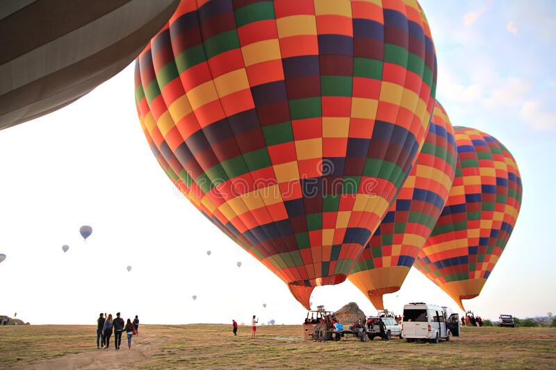Preparing for take-off hot air balloons with tourists on sunrise.  royalty free stock photography