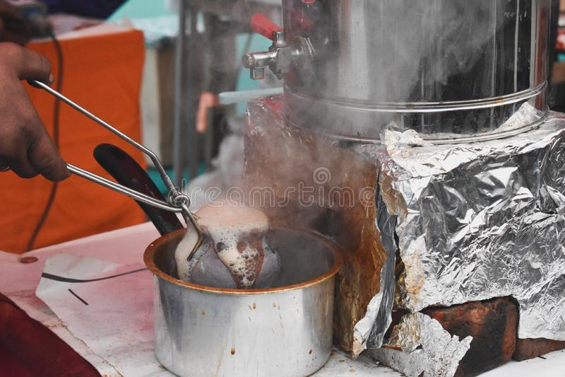 Preparing Tandoori tea in hot earthenware pot royalty free stock photos