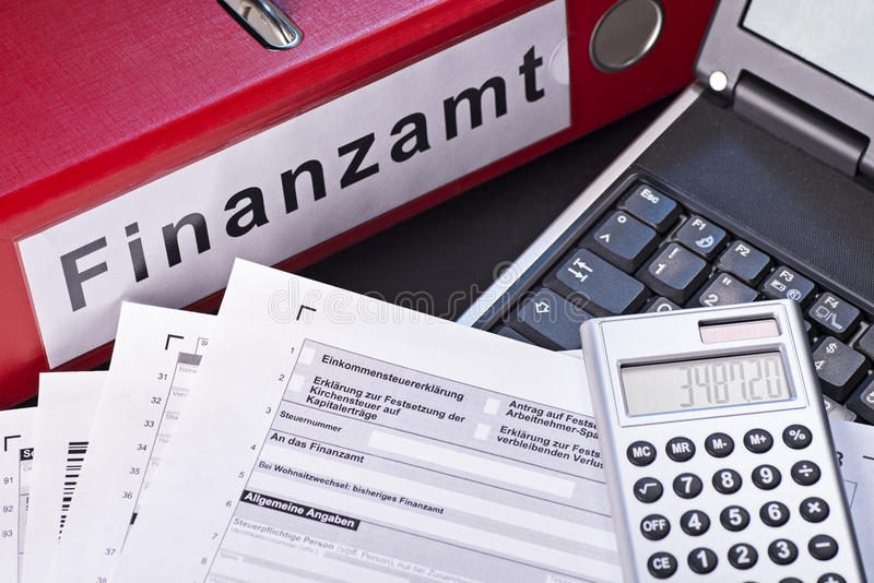 Preparing the tax return. File folder labeled Finanzamt (tax office), forms, calculators and a computer as a symbol for the preparation of the tax return royalty free stock photography