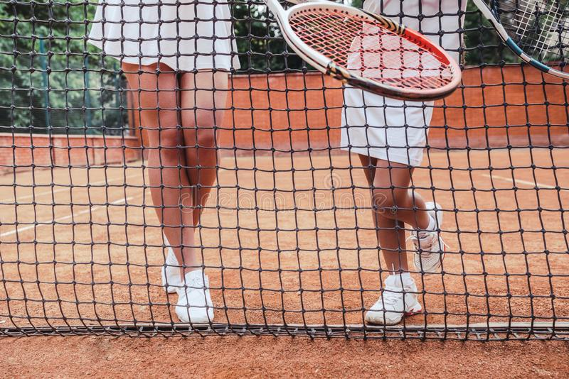 Preparing to big game! Cropped image of sporty woman and girl legs while standing behind net on tennis court. Female trainer and stock images