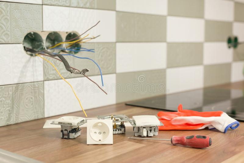 Preparing to install an electrical outlet. Closeup of professional electrician tools and electrical outlets. Renovation and stock photo