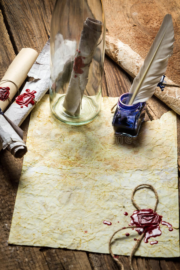 Preparing to send ancient letter in a bottle and writting with b stock image