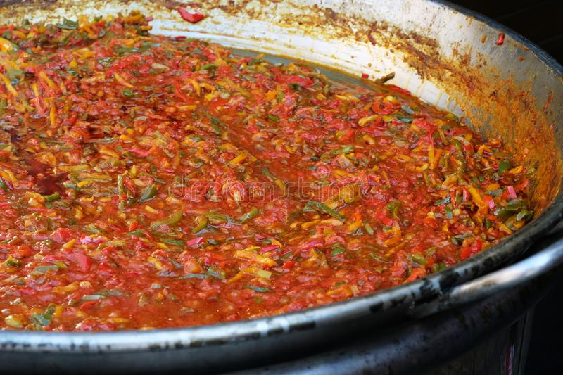Preparing the vegetable and spice base for delicious paella - traditional spanish food - on the street royalty free stock images