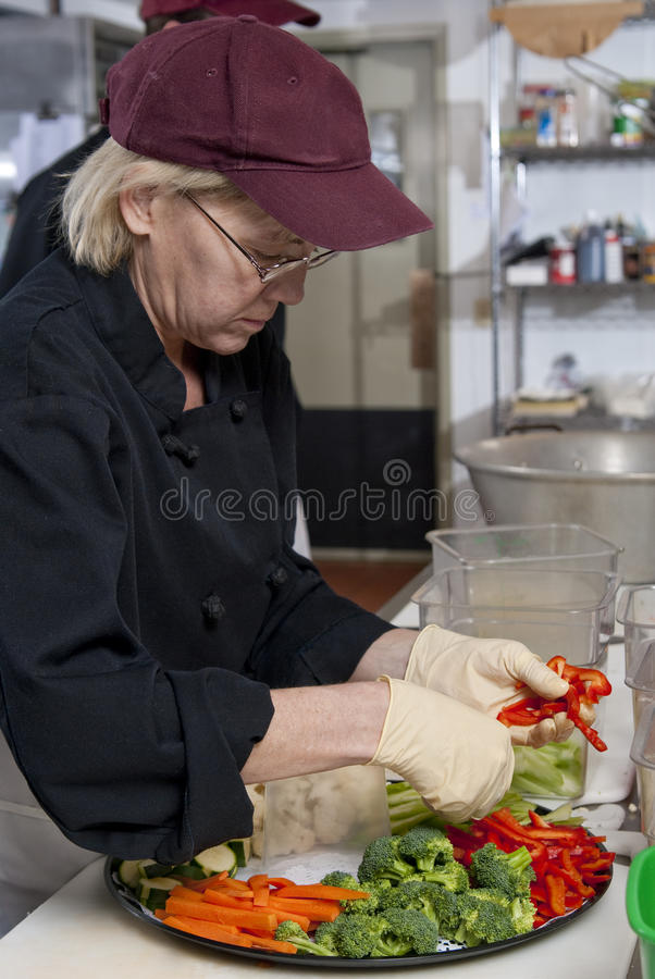 Preparing a veggie platter. A food service worker places vegetables on a tray stock photo