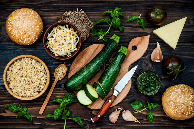 Preparing veggies cutlets or patties for burgers. Zucchini quinoa veggie burger with pesto sauce and sprouts. Top view, overhead. Raw ingredients for vegetarian royalty free stock image