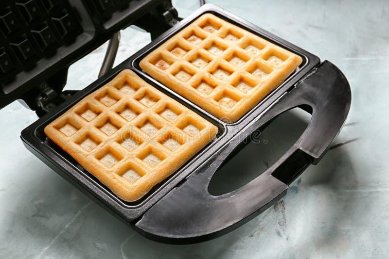 Preparing of waffles in modern maker on light table stock images