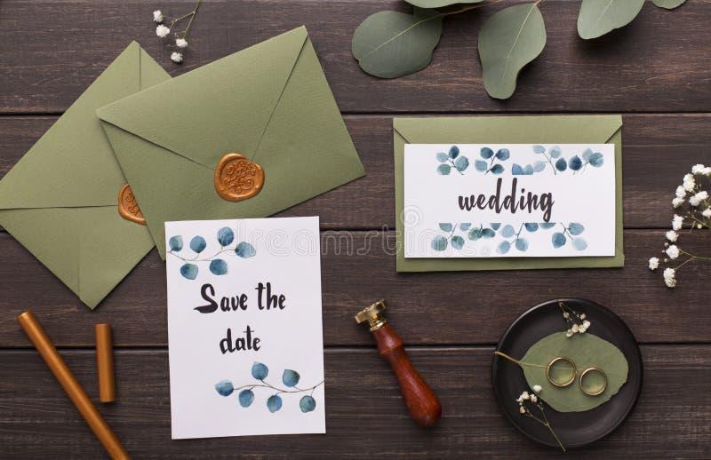 Preparing wedding invitations and folding envelopes on wood. En table background stock photo