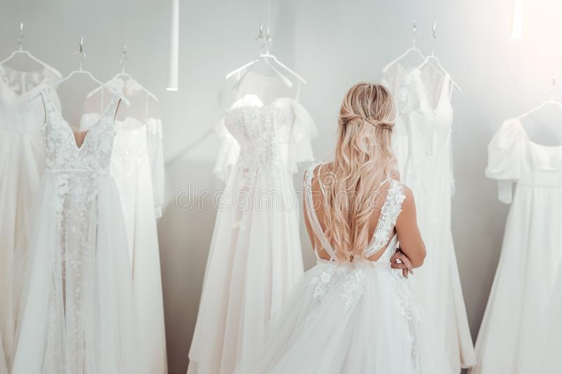 Young bride standing in front of wedding dresses. stock images
