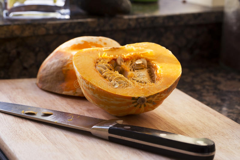 Preparing Winter Squash. Winter squash cut in half with knife on cutting board royalty free stock photography