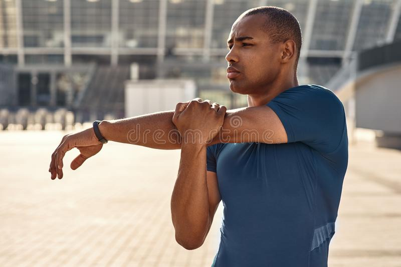 Preparing for workout. Close up portrait of african athlete stretching his arms during morning workout stock photo