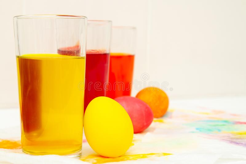 Prepearing for Easter. coloring painting eggs in glasses with color Yellow, red, orange. copyspace.  royalty free stock images