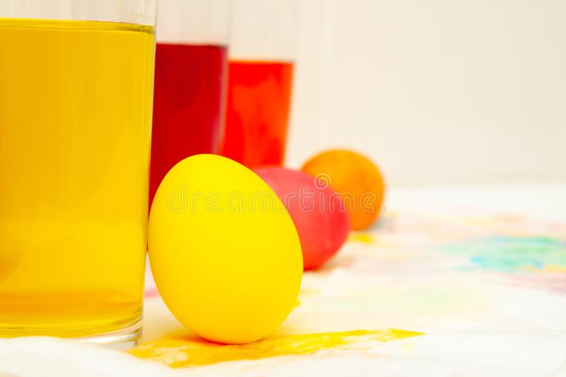 Prepearing for Easter. coloring painting eggs in glasses with color Yellow, red, orange. copyspace.  stock image