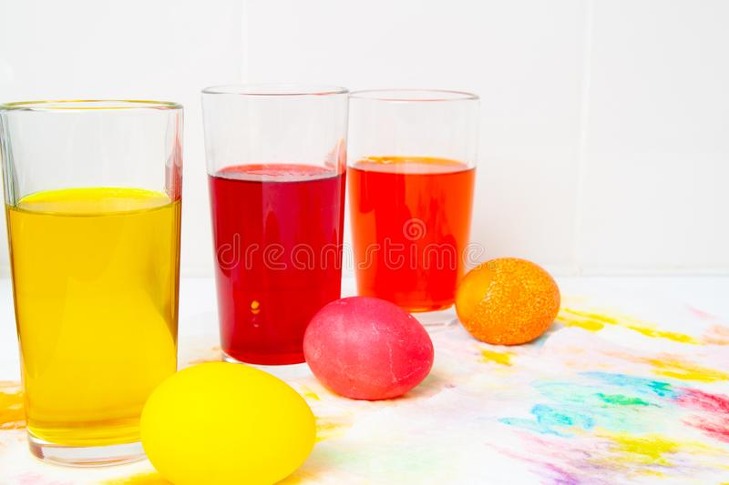 Prepearing for Easter. coloring painting eggs in glasses with color Yellow, red, orange. copyspace.  royalty free stock image