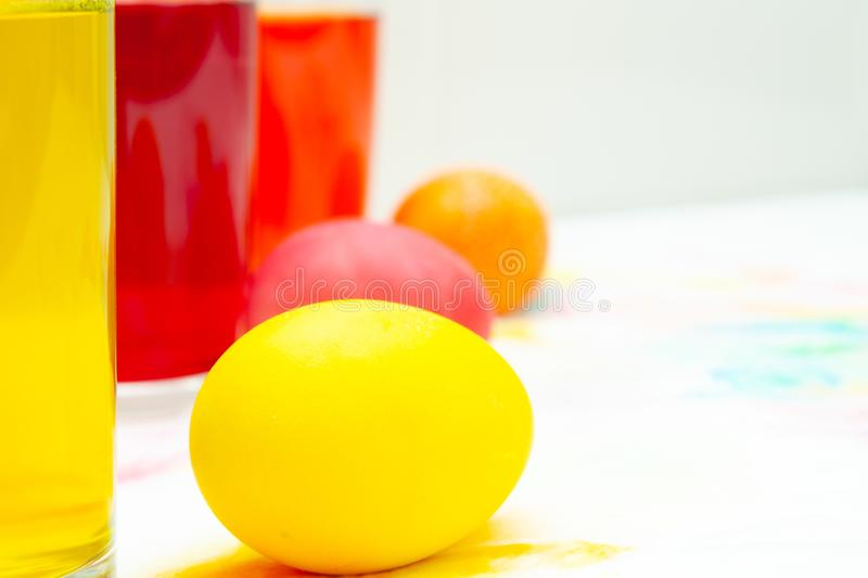 Prepearing for Easter. coloring painting eggs in glasses with color Yellow, red, orange. copyspace.  stock photo