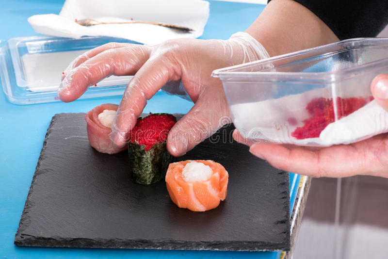 Prepearing Gunkan maki sushi. Chef in kitchen cooking maki rolls holding plastic container with red caviar, hands in gloves royalty free stock photo