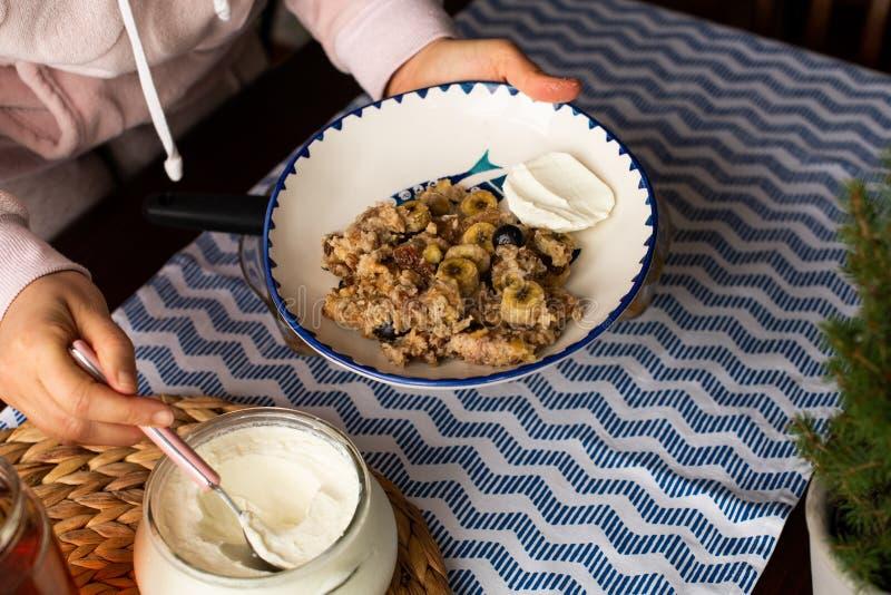preperation da farinha de aveia cozida com banana, mirtilos, noz e passas servido com iogurte e mel Mel do gotejamento pôr foto de stock